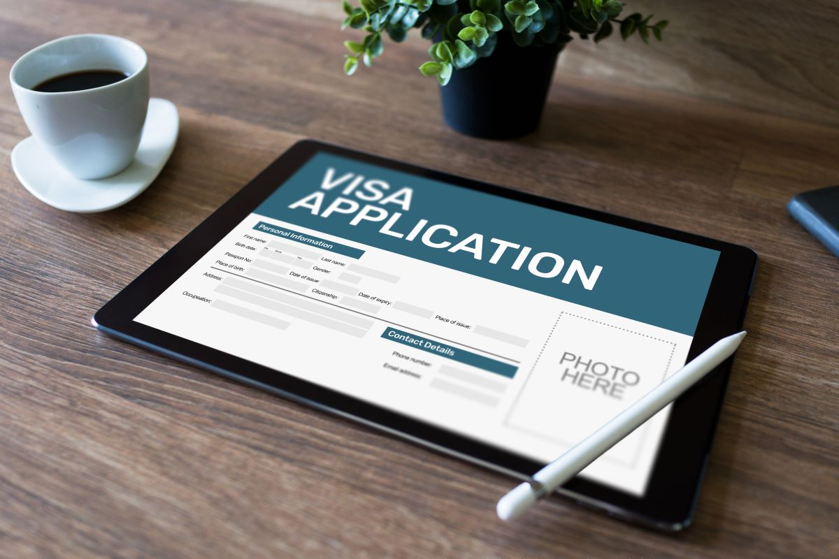 ipad with online visa application on desk with coffee cup and plant
