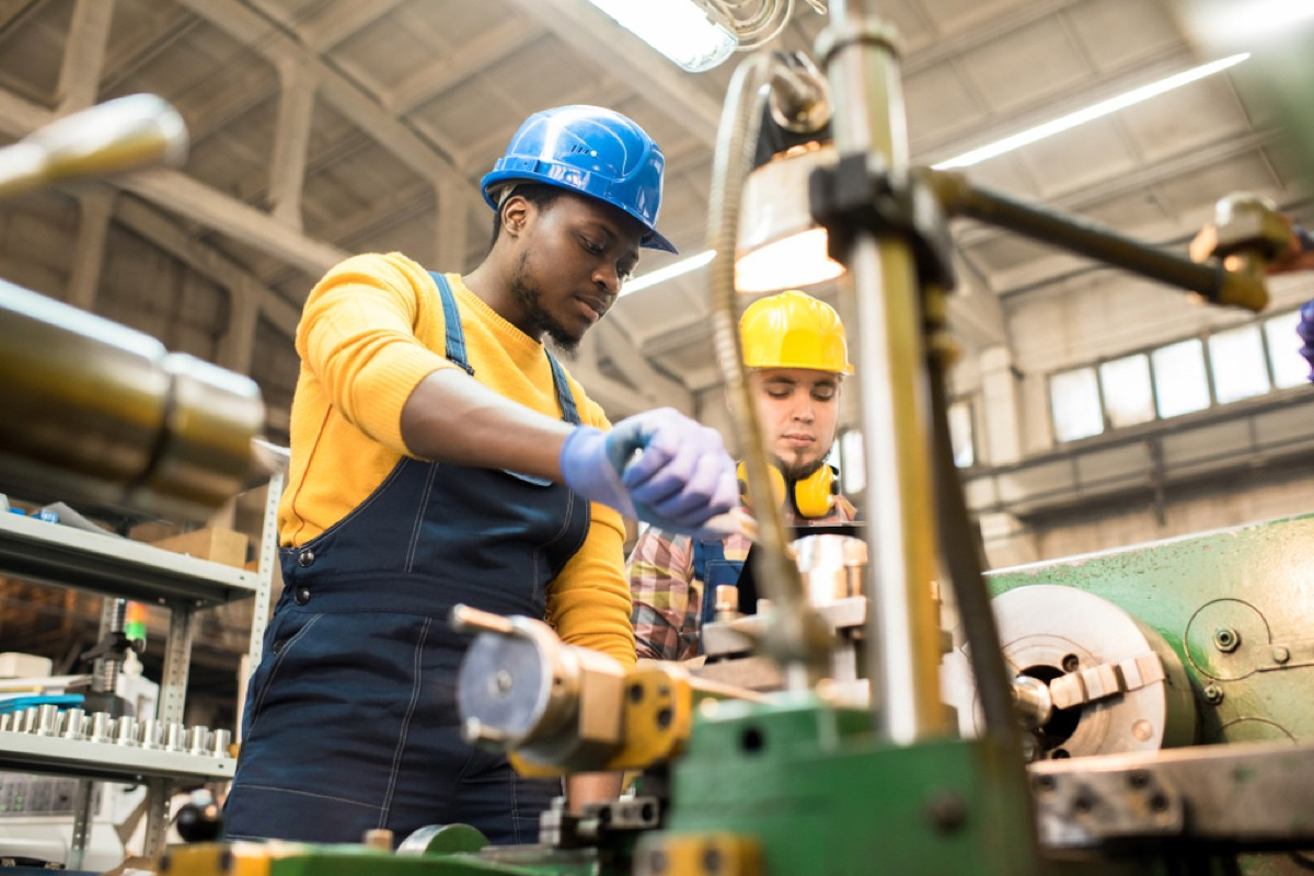 skilled workers operating machines in factory wearing yellow safety gear