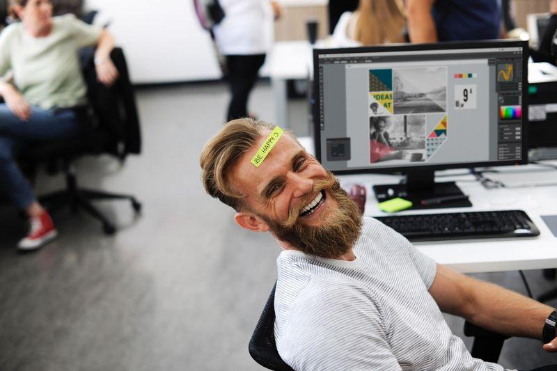 happy man at desk at work in Canada | Canada Visa Application