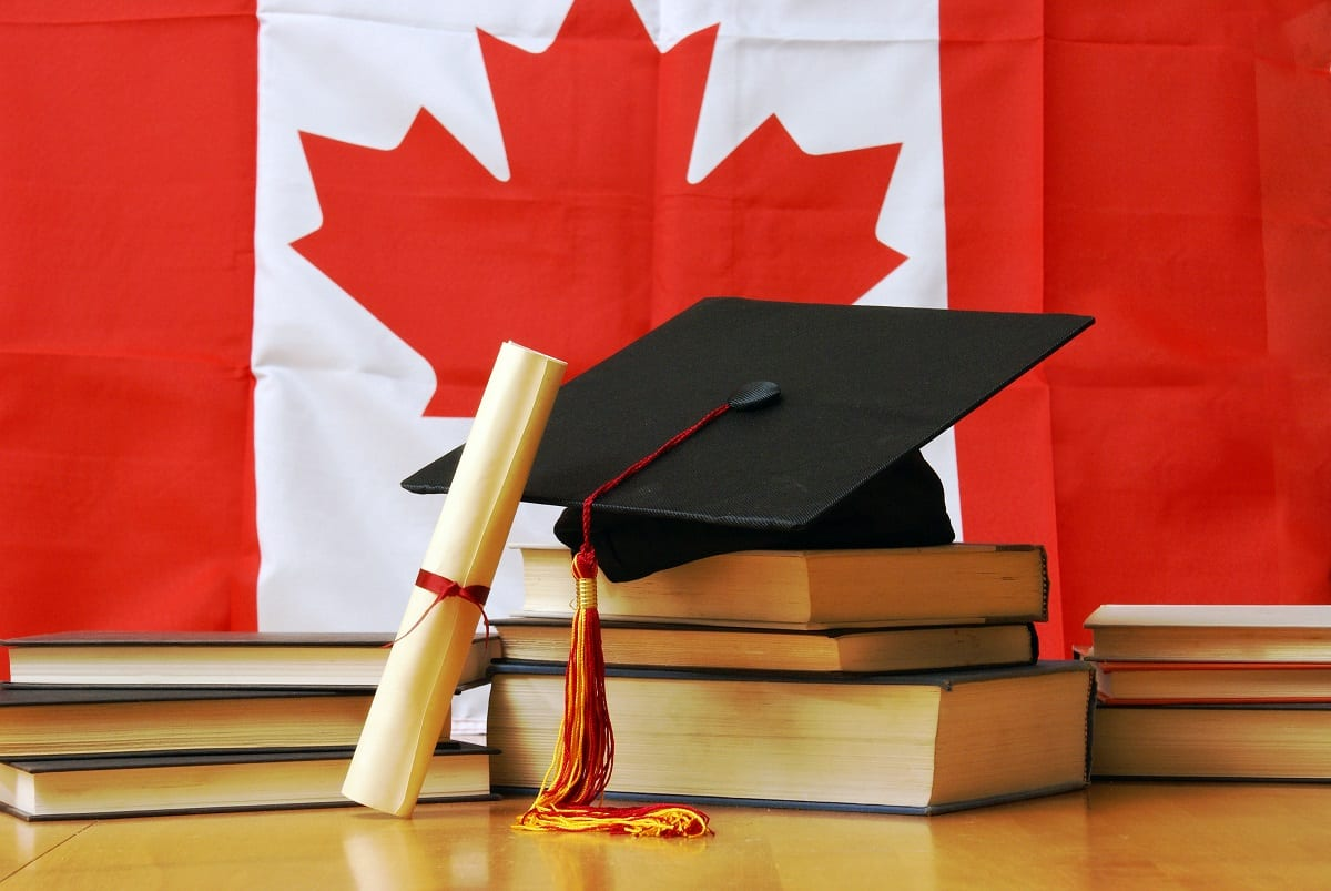 graduation cap and diploma in front of Canadian flag