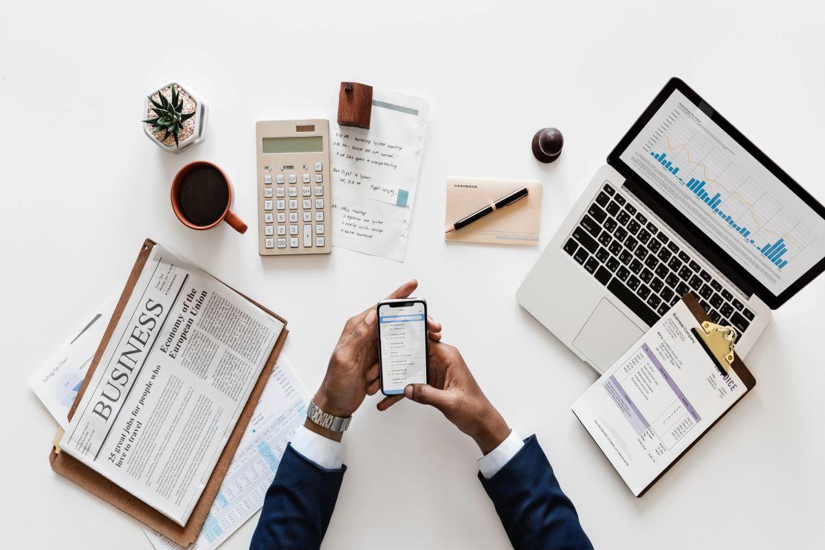 marketing executive planning laptop newspaper cellphone coffee plant desk