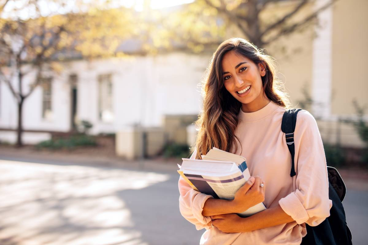 beautiful smiling female student holding textbooks | study in Canada