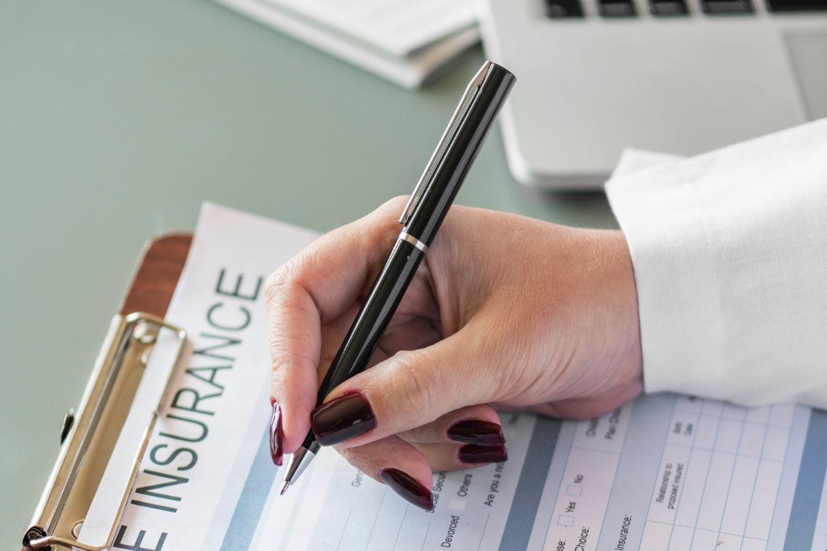 women filling in insurance form