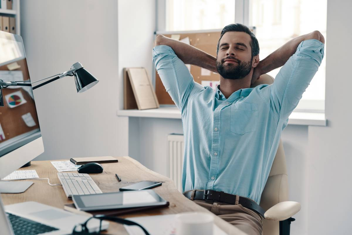 man relaxing at desk at work in Canada | jobs in Canada