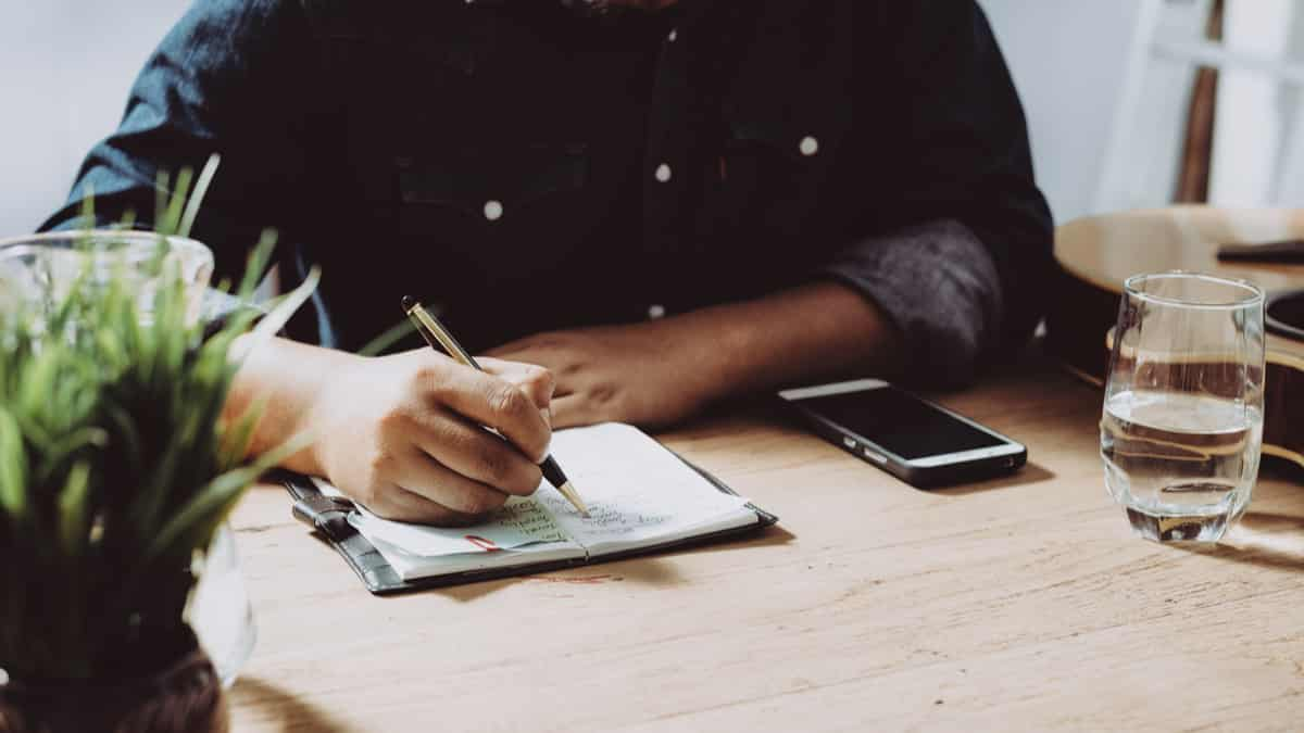 man-completeling-checklist-in-journal-at-desk | immigrate to Canada