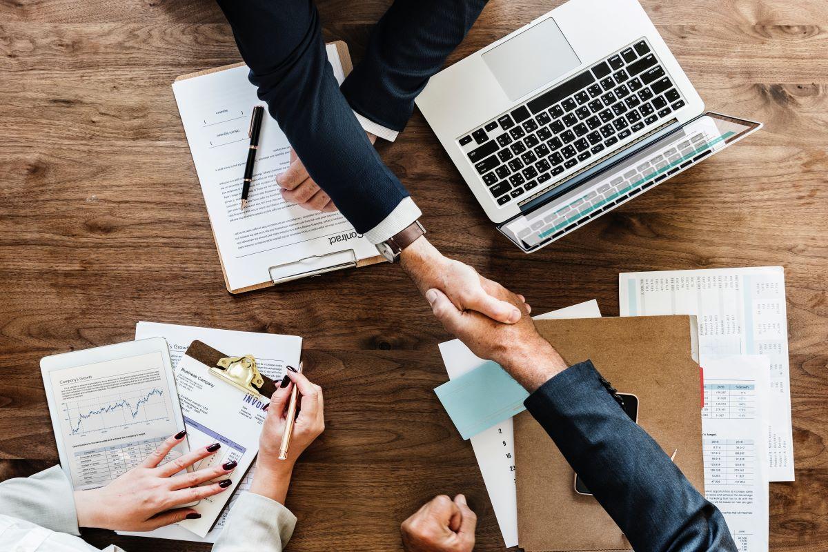 handshake desk laptop documents
