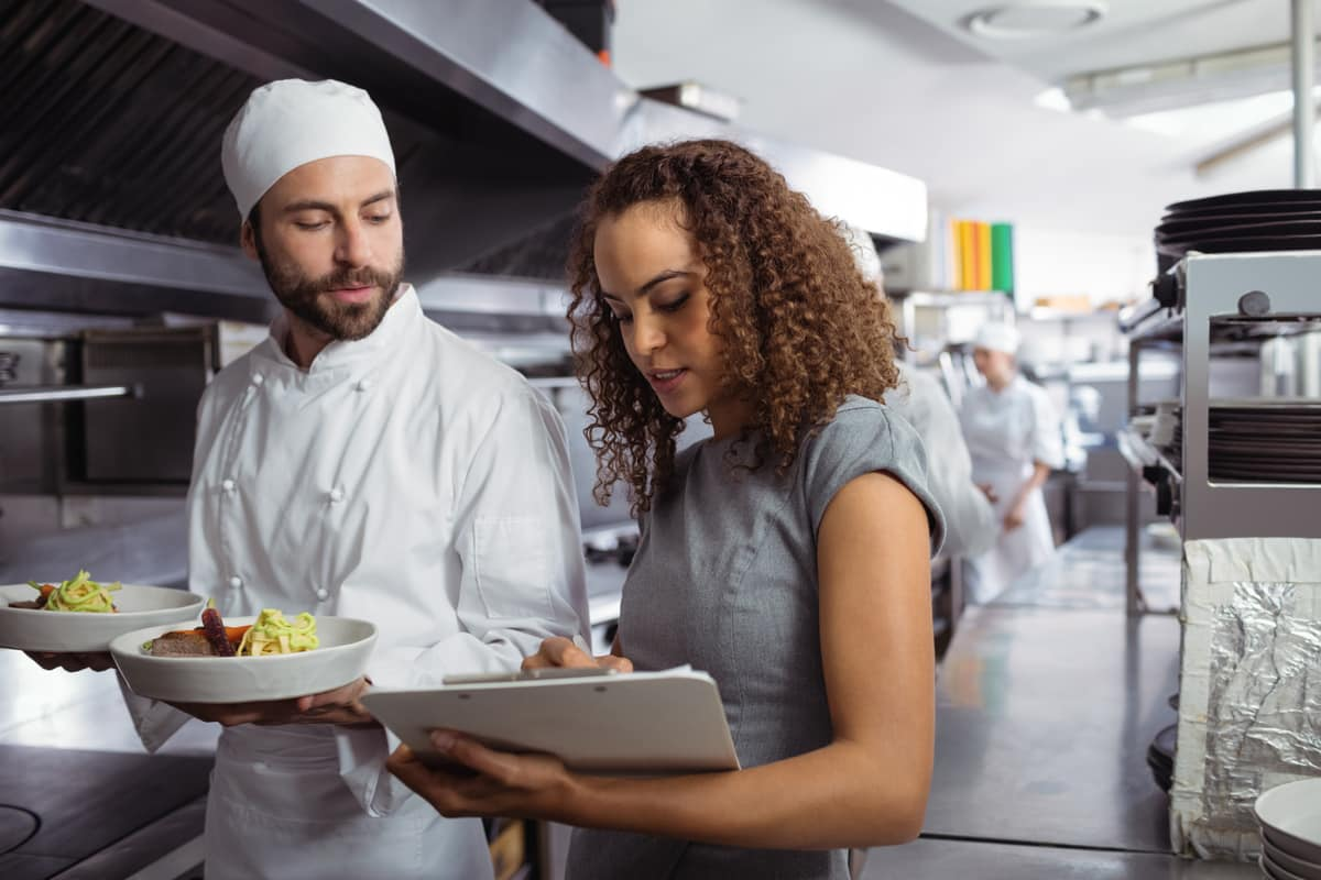 Female restaurant manager speaking to chef