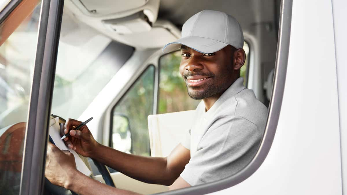 smiling truck driver in truck | immigrate to Canada