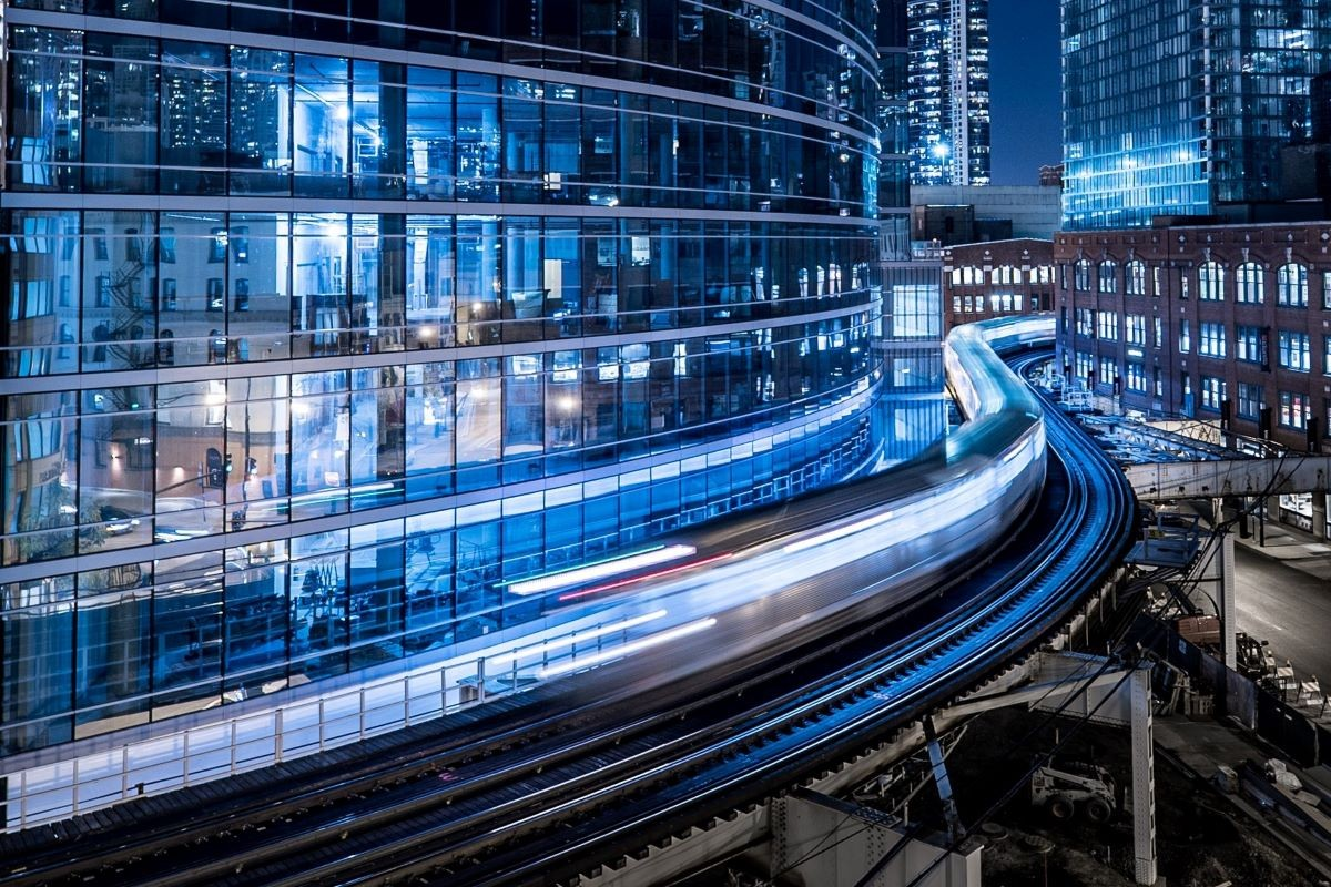 speeding train in front of office building windows blue
