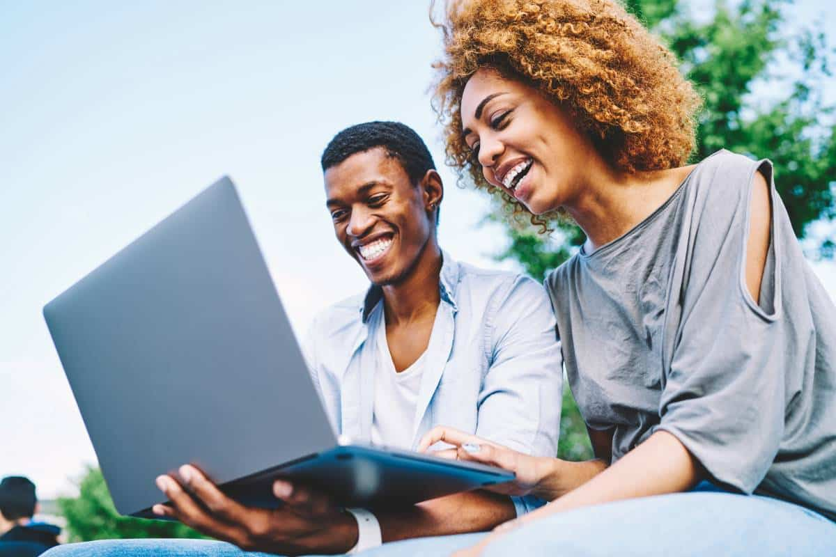 two people smiling and typing on laptop | how to immigrate to Canada