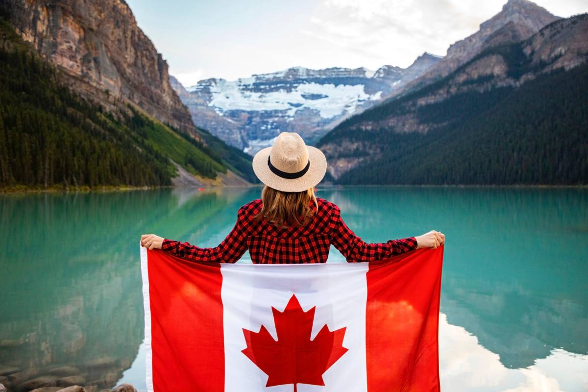 woman holding Canadian flag in front of river and Canadian Rockies