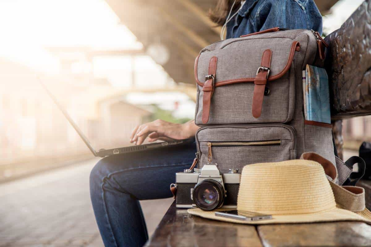woman typing on laptop with backpack camera and hat on bench | plan your gap year in Canada