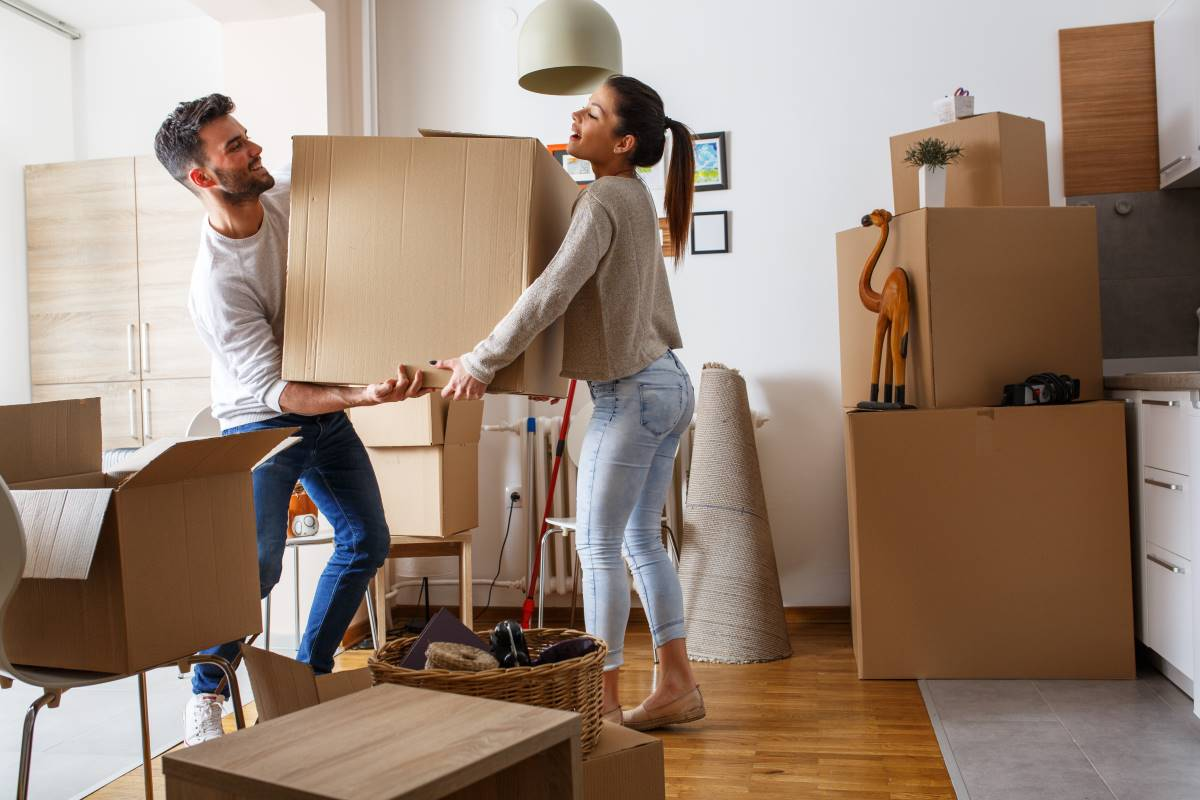 Young couple moving boxes into new home in Canada