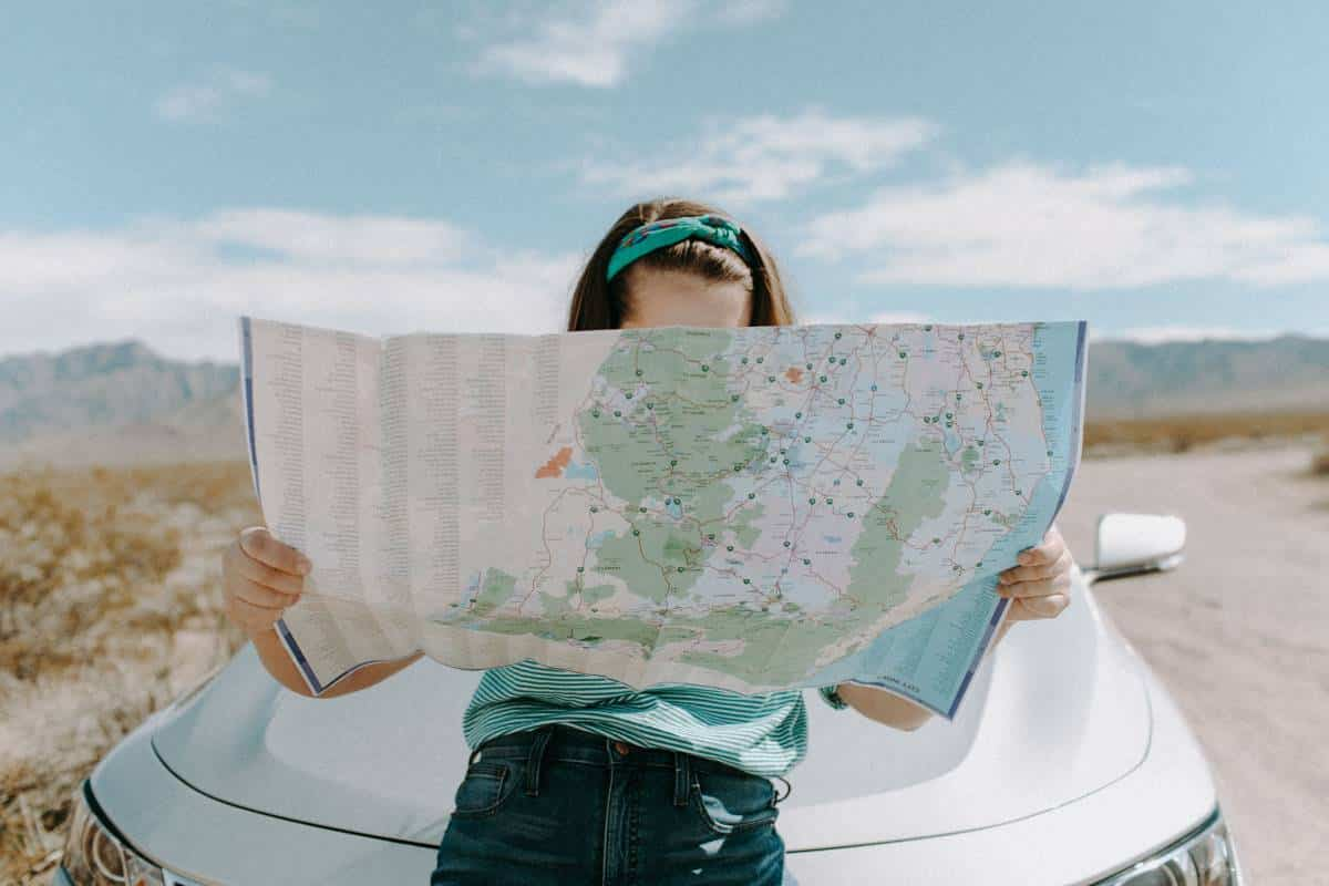 young woman on road trip looking at map | plan your gap year in Canada